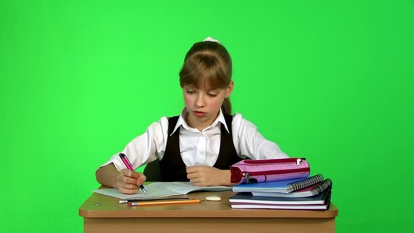 Schoolchild girl writing in notebook. Chroma key on green background.