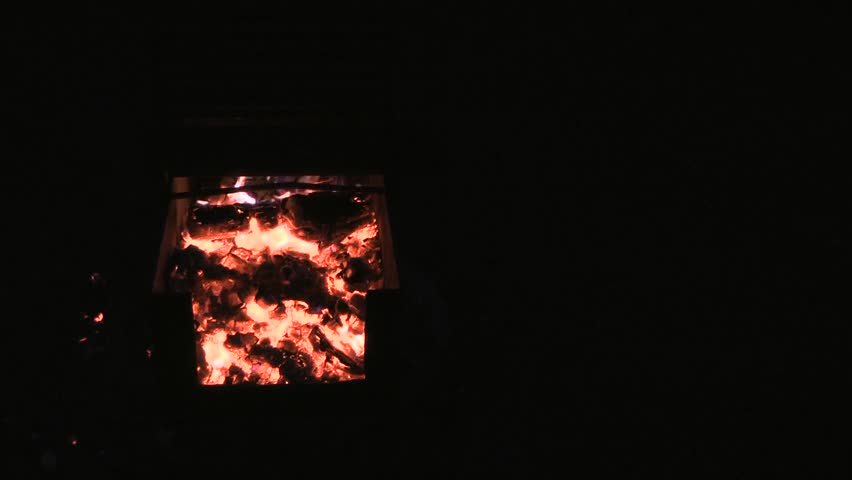 Embers of coal with black background on right. Campfire closeup. Natural background - HD stock footage clip