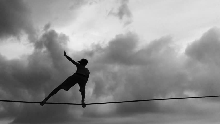 Silhouette of person on slackline in slow motion against cloudy skies in black and white