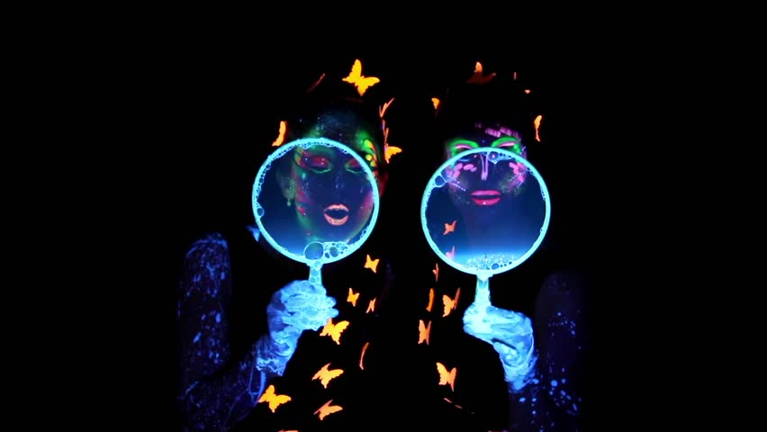 Video of two woman with luminous make up blowing bubbles in camera in darkness - HD stock footage clip