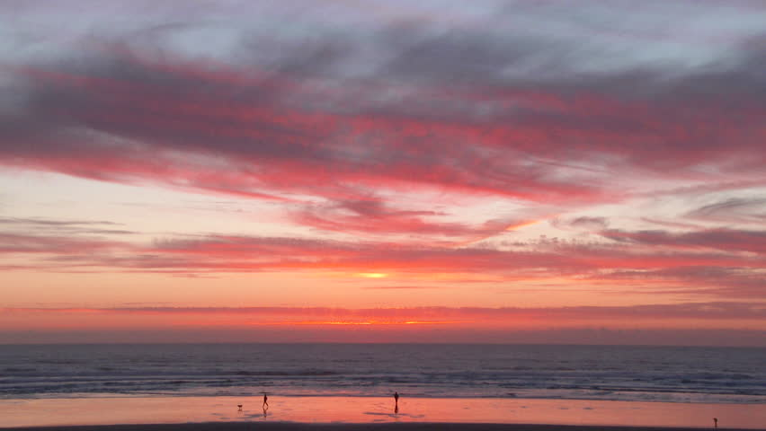 Silhouetted man and woman play with their dog, enjoying sunset at beach together in Oregon, wide angle.