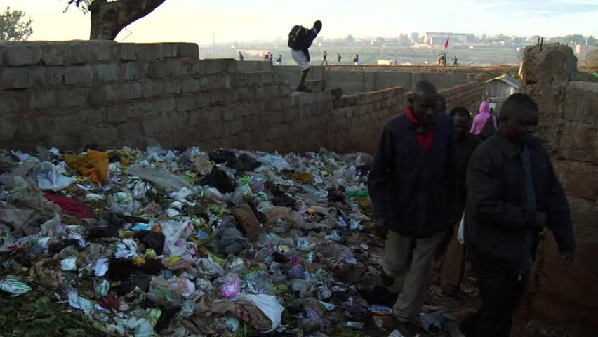 NAIROBI, KENYA - CIRCA JULY 2009: Kenyans walk near piles of trash. Shot in high definition.