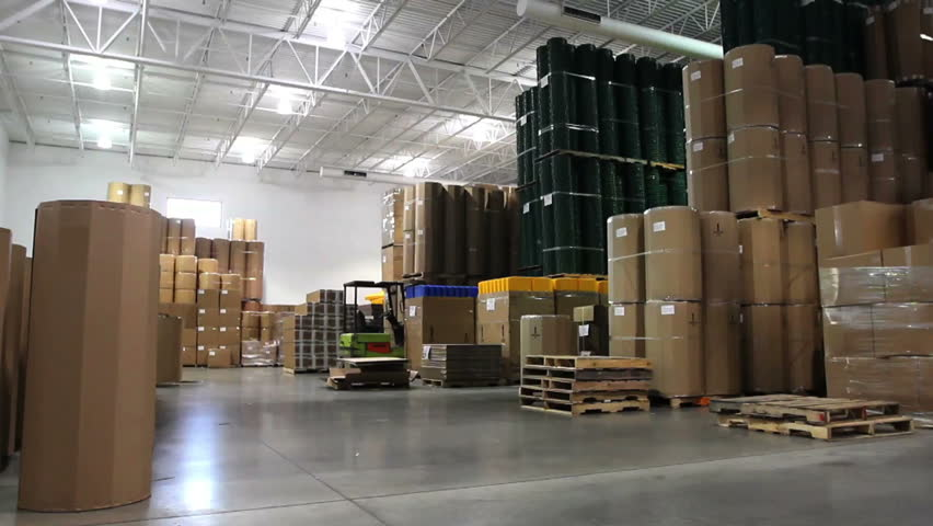 A forklift driver cruises through a large factory warehouse.  - HD stock video clip