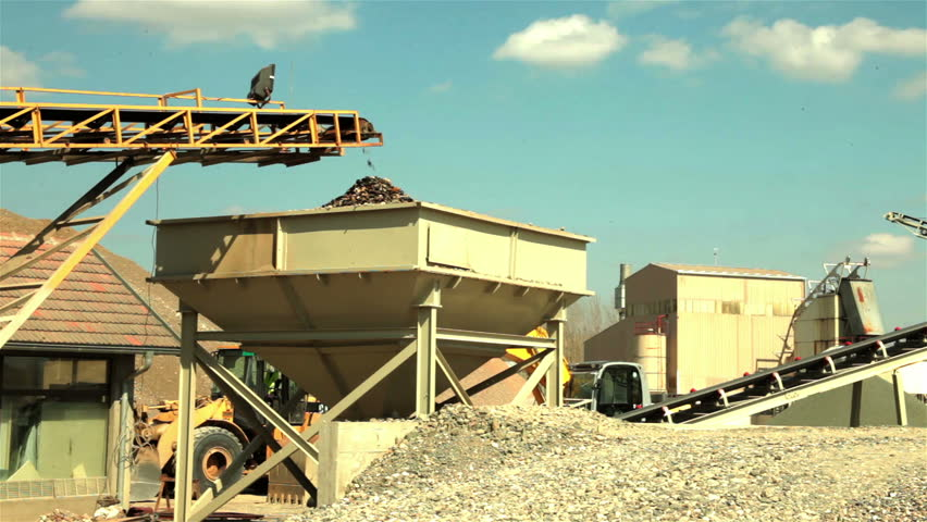 Separation of sand in the construction industry. Sand and stones falling from conveyor belt and forming pile of sand. Beautiful landscape with blue sky in background. Preparation sand. Low angle view.