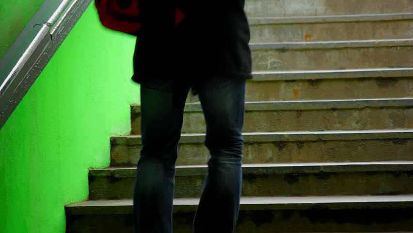 Young male on dark green staircase. Man in jeans and sneakers walking up the stars. Source: Canon 7D, graded. Clip ID: ax1221c