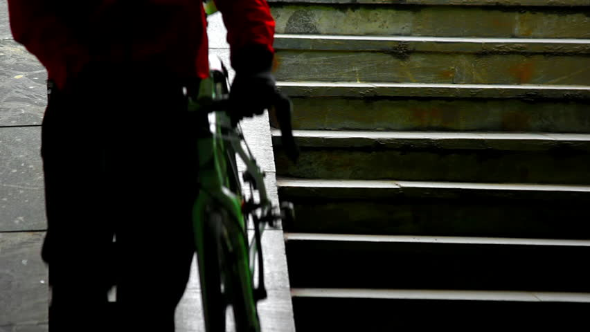 Man rolls the bike down the stairs to the subway. Source: Canon 7D, graded. Clip ID: ax1223c