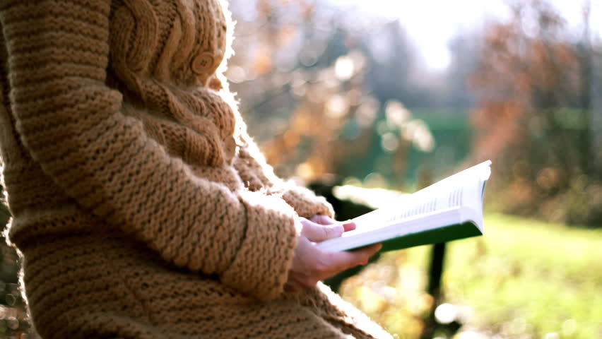 Woman sitting in the park and reading book, camera stabilizer shot  - HD stock video clip