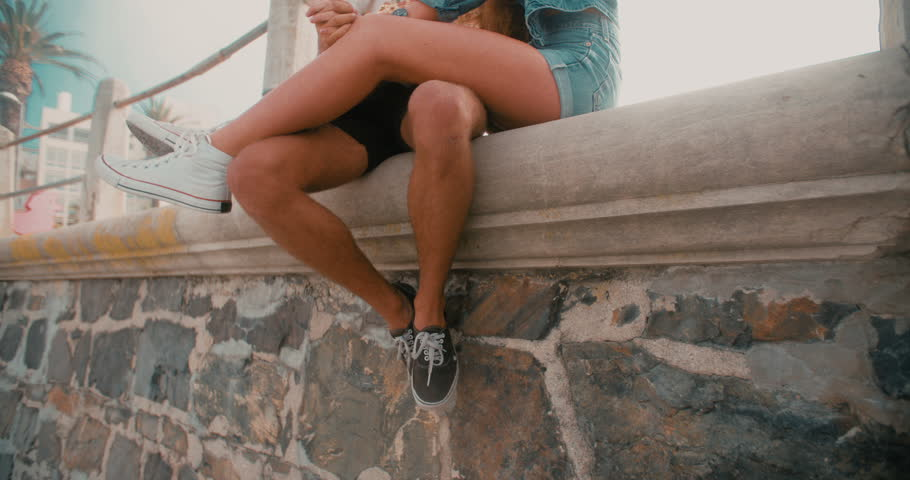 Cropped slow motion video of the legs of a hipster couple holding hands and sitting on a wall made of rough textured stone