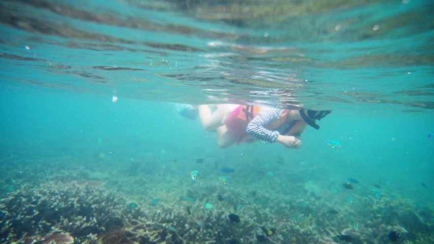 girl with mask snorkeling in clear water