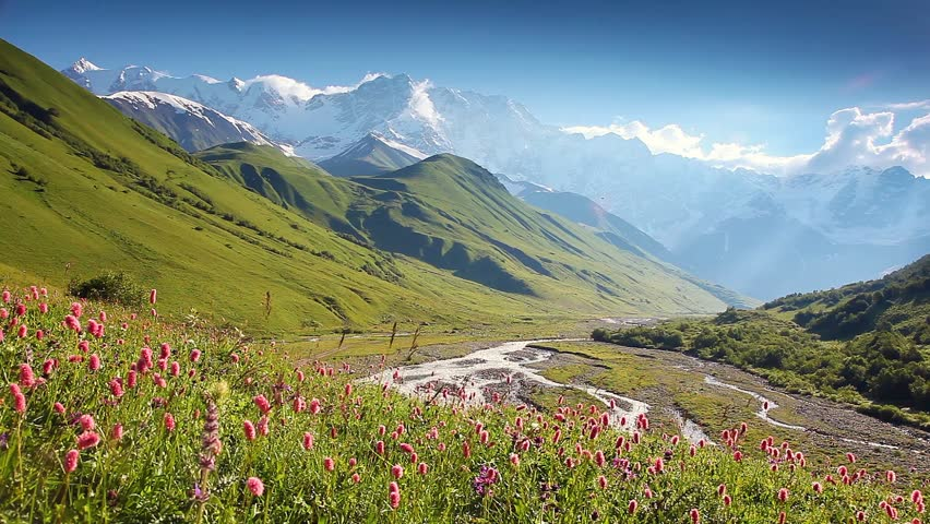 Green meadows with blue sky at the foot of Mt. Shkhara. Upper Svaneti, Georgia, Europe. The main Caucasus ridge. Dramatic unusual scene. Beauty world. HD video (High Definition)