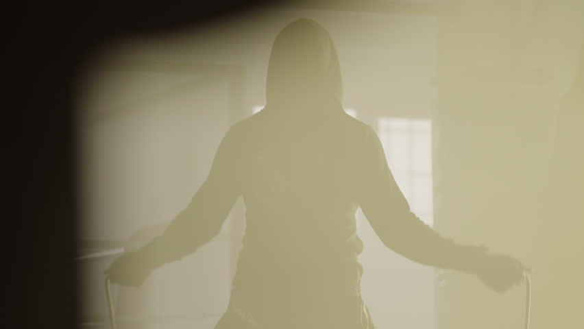 Hooded woman skipping with her back towards camera, in a boxing club with a ring at background.