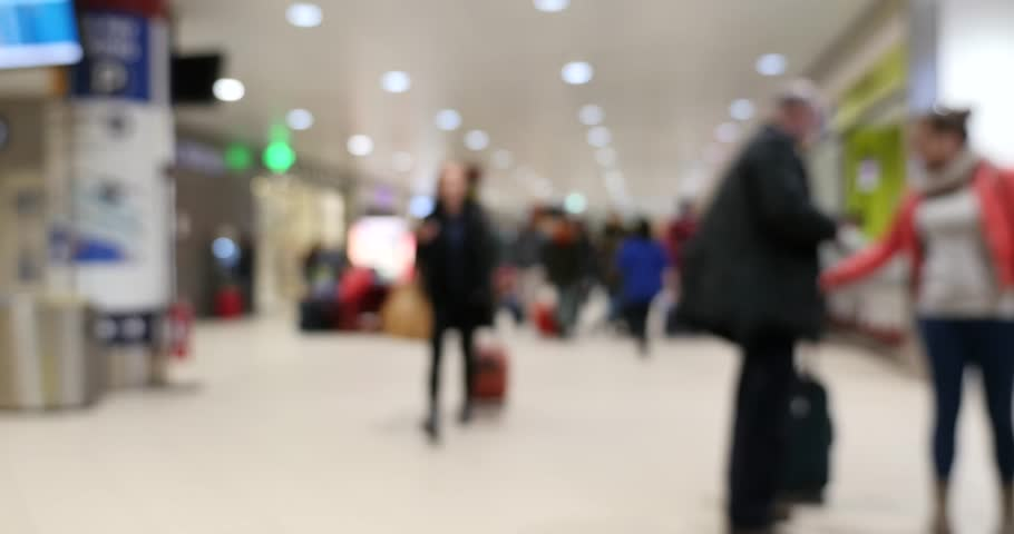 Unidentified blurred image of people walking inside airport.