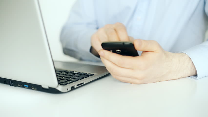 Man using mobile phone and laptop.