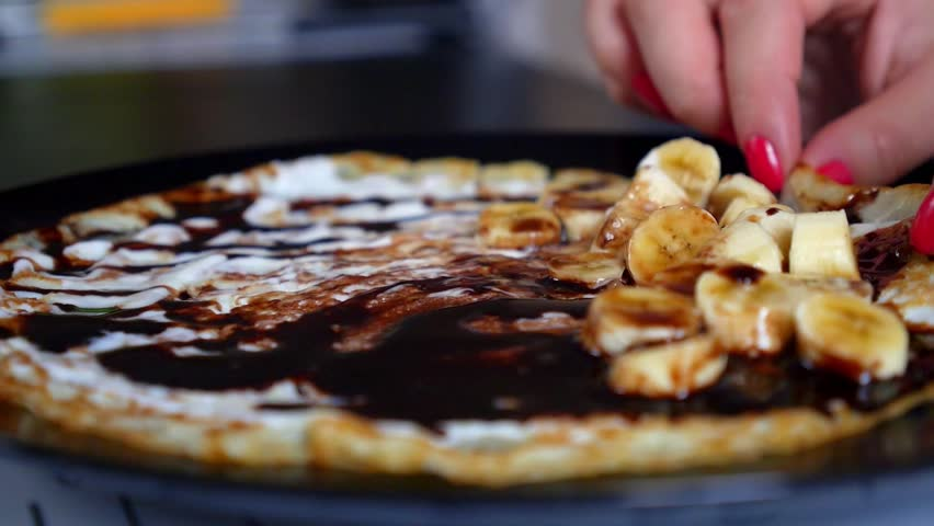 Close-up Wrapping Chocolate Crepes with Sauce and Bananas on the Plate. HD, 1920x1080.   - HD stock video clip