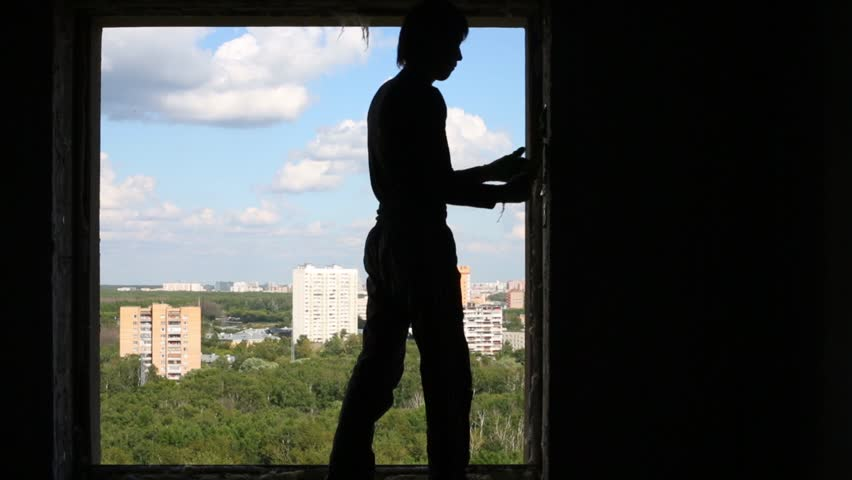 Silhouette of worker with spatula in his hand who cleans window aperture.