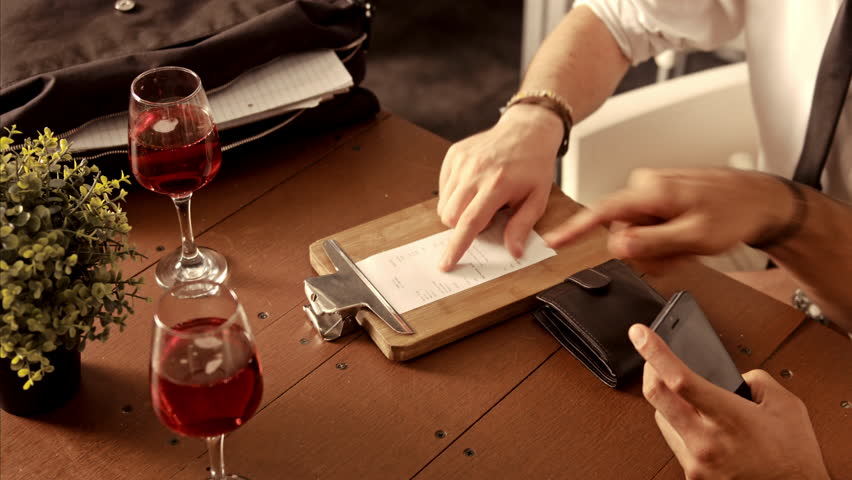 Waiter in a restaurant brings a credit card reader to the table for the bill to be paid.