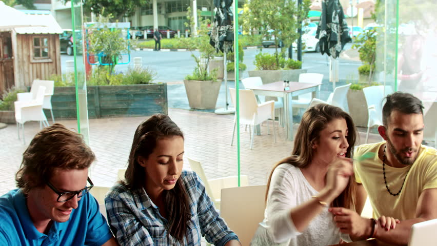 Steadicam/panning shot of young multicultural group of fellow creative students brain storming at cafe, wile using technology to study.