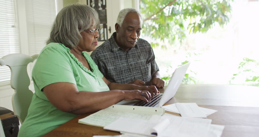 Mature African couple payign bills on laptop - 4K stock footage clip