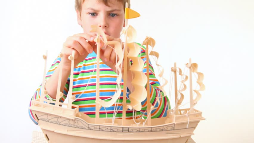 boy sets up sails of toy model of ship on white background - HD stock footage clip