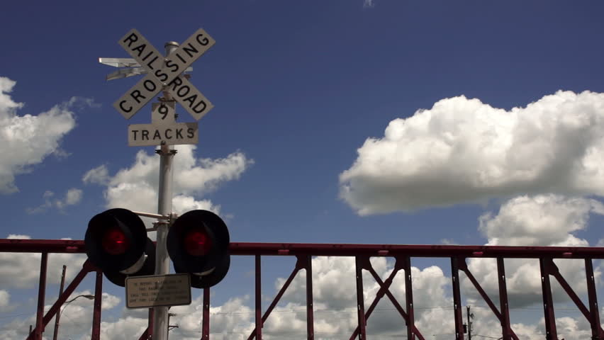 Train Passing Railroad Crossing Warning Lights Flashing Fluffy Clouds Rolling By - HD stock footage clip
