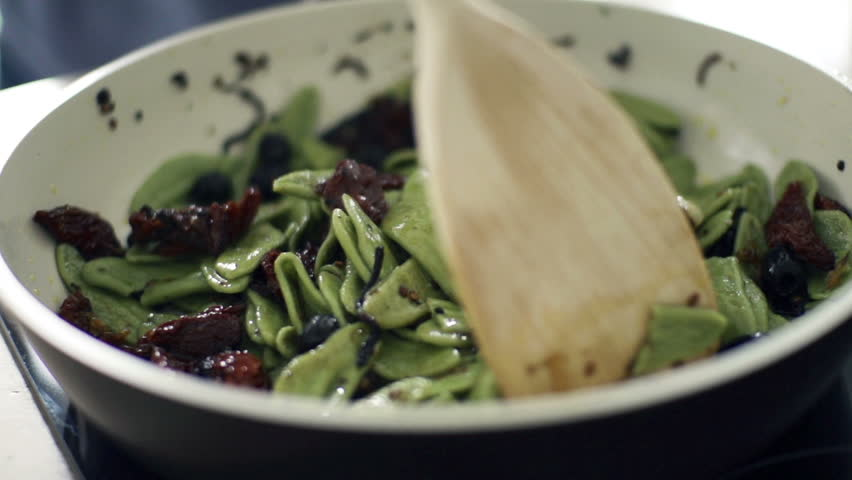 Cooking, mixing pasta and olives on pan, slow motion shot at 240fps
