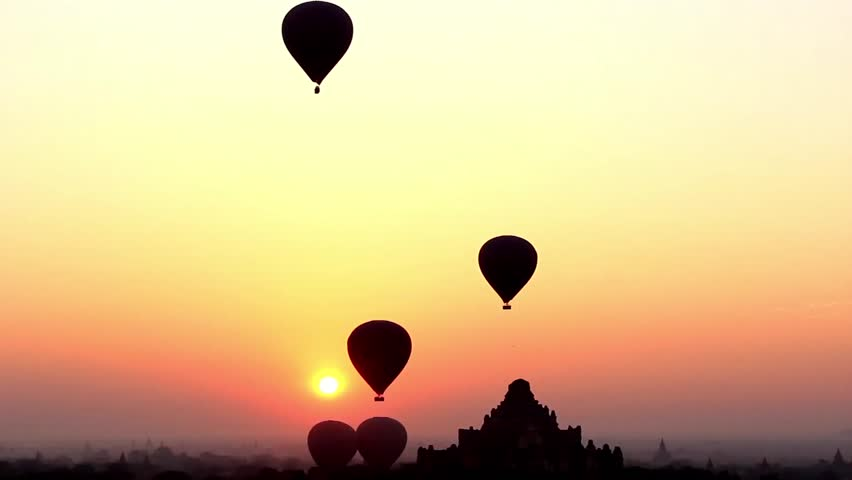 Air balloons go up in sunrise in Bagan, Myanmar (Burma). Magic sunrise with air balloons and spectacular colors.
