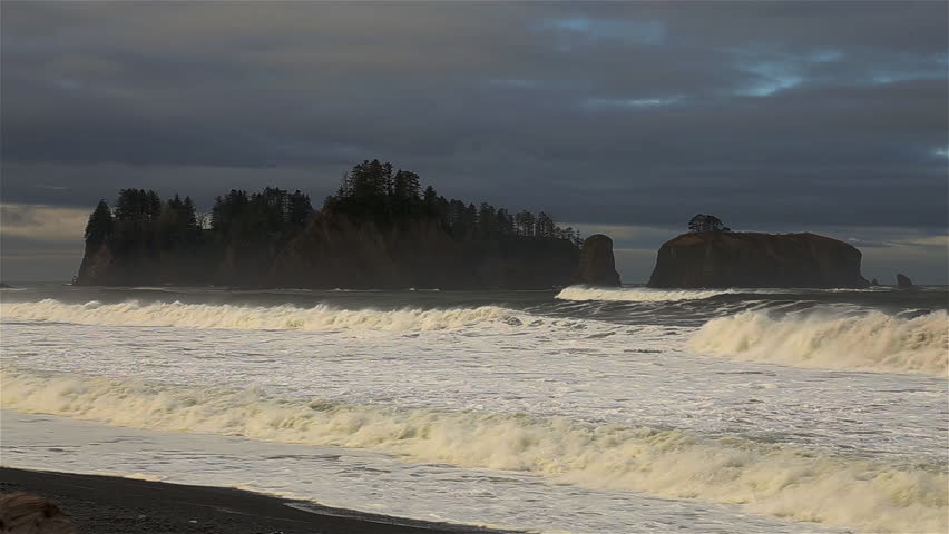 Waves breaking with rock formation by the ocean of Pacific coast. Rialto Beach, Olympic National Park, Washington State, USA