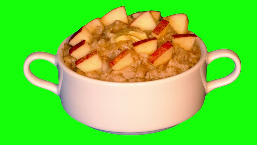 Hot porridge with butter and pieces of apple in bowl rotating on green screen, loop, front shot