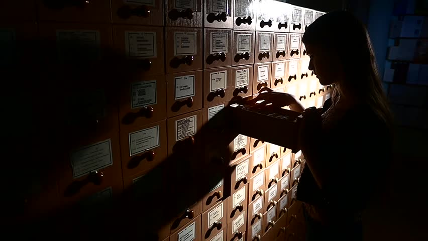 Searching in archives. Student searching from a filling cabinet. Light falls on boxes, girl with long hair, slow motion