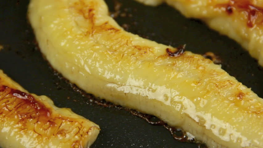 Zoom back from slices of fresh banana being fried in a pan.