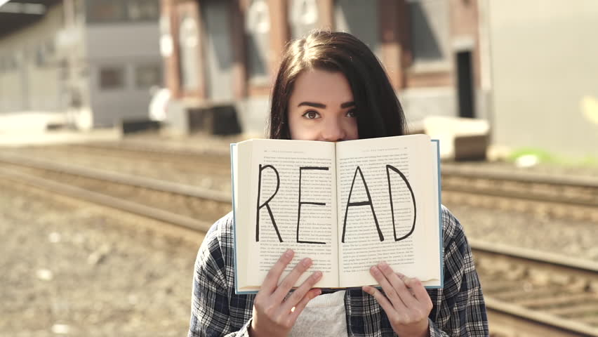 Mixed Race Teen Holds Up Book In Front Of Her Face, It Says READ On The Pages (Slow Motion)